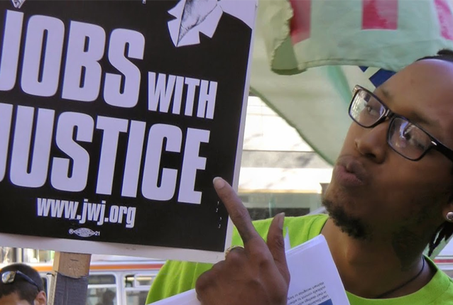 Dominic Ware, an OUR Walmart member fired after participating in strikes last year, holds a Jobs With Justice sign at last week's rally. Photo by Peter Menchini.